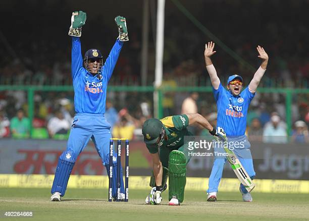 India`s captain MS Dhoni and Suresh Raina appeal to umpire against South Africa's Faf du Plessis during the first One Day International match between...