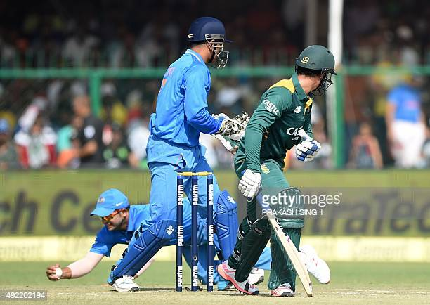 India's captain Mahendra Singh Dhoni and South Africa's Quinton de Kock look back as India's Suresh Raina takes a catch to dismiss de Kock during the...