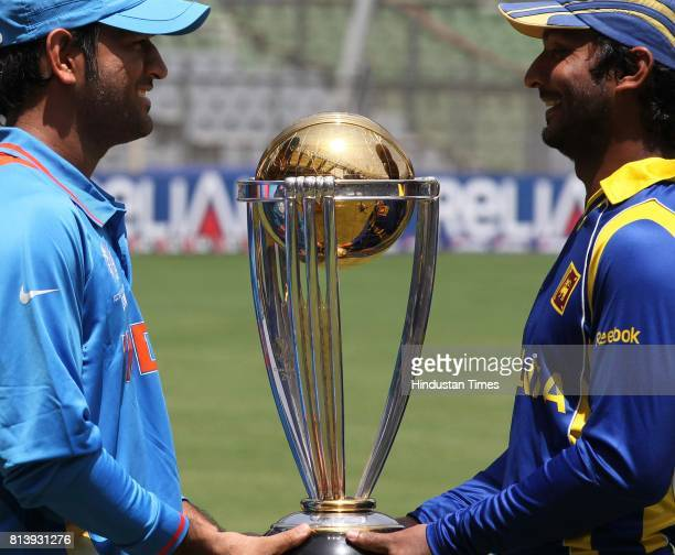 India's captain Mahendra Singh Dhoni and Sri Lanka captain Kumar Sangakkara poses with cricket world cup trophy ahead of their ICC Crciket World Cup...