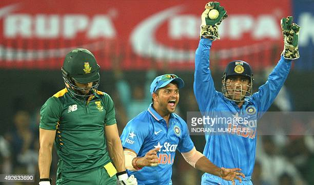 India's captain Mahendra Singh Dhoni and Suresh Raina appeals successfully for a caught behind of South Africa's Farhaan Behardien during the second...