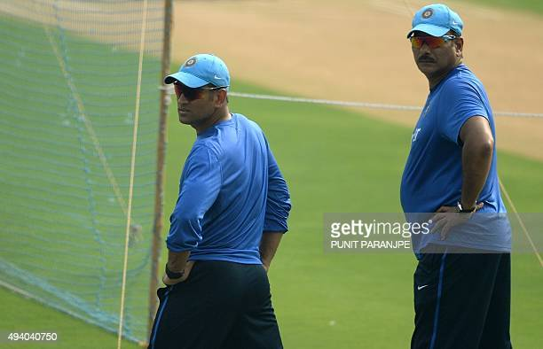 India's captain Mahendra Singh Dhoni and team director Ravi Shastri watch players during a training session on the eve of the fifth one day...