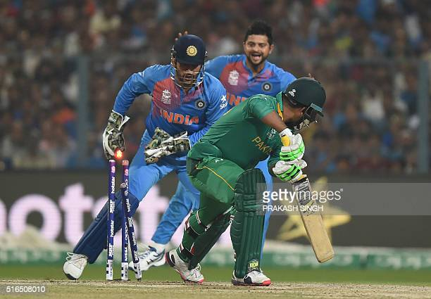 India's captain Mahendra Singh Dhoni and teammate Suresh Raina look on as Pakistan's Sharjeel Khan plays a shot during the World T20 cricket...