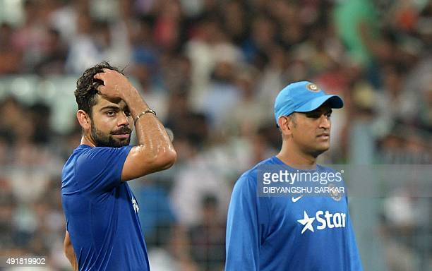 India's captain Mahendra Singh Dhoni and teammate Virat Kohli look on ahead of the start of the third T20 cricket match between India and South...