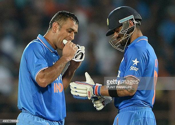 India's captain Mahendra Singh Dhoni bites his glove during a break at the third one day international cricket match between India and South Africa...