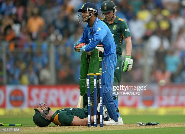 India's captain Mahendra Singh Dhoni helps South Africa's Faf du Plessis to stretch after du Plessis suffered from cramp while batting during the...