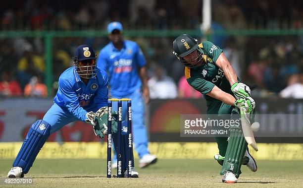 India's captain Mahendra Singh Dhoni looks on as South Africa's captain AB de Villiers plays a shot during the first one day international cricket...