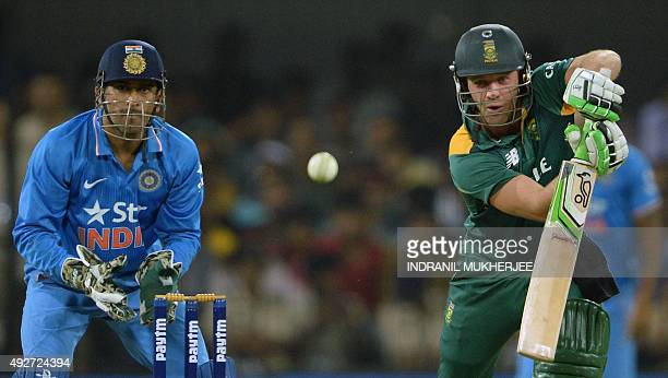 India's captain Mahendra Singh Dhoni looks on as South Africa's captain AB de Villiers plays a shot during the second one day international cricket...