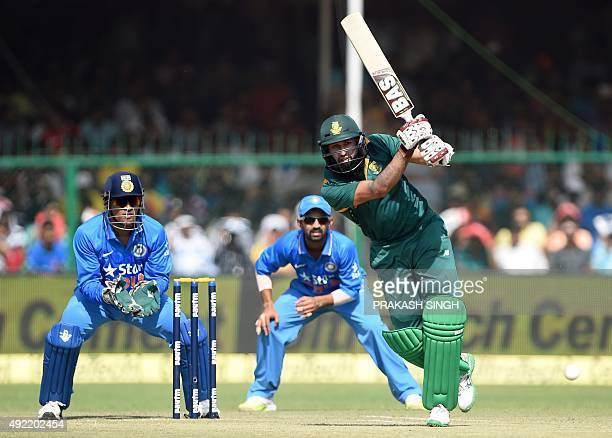 India's captain Mahendra Singh Dhoni looks on as South Africa's Hashim Amla plays a shot during the first one day international cricket match between...