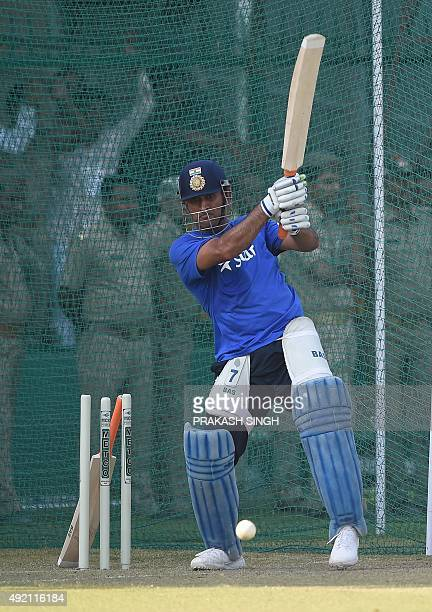 India's captain Mahendra Singh Dhoni plays a shot in nets during a training session on the eve of the first one day international cricket match...
