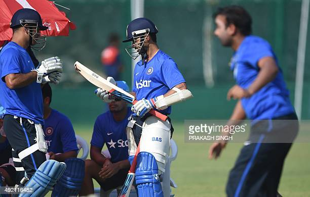 India's captain Mahendra Singh Dhoni talks with Ajinkya Rahane as Amit Mishra bowls during a training session on the eve of the first one day...