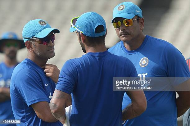 India's captain Mahendra Singh Dhoni talks with cricketer Virat Kohli and director of Indian Cricket Team Ravi Shastri during a training session on...