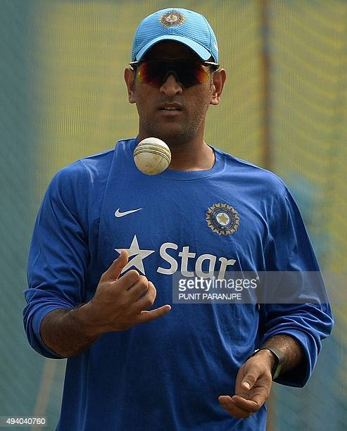 India's captain Mahendra Singh Dhoni tosses a ball as he attends a training session on the eve of the fifth one day international cricket match...