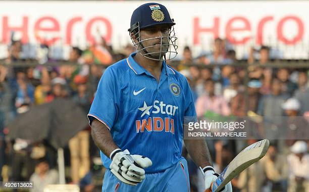 India's captain Mahendra Singh Dhoni walks back at the end of their quota of 50 overs during the second one day international cricket match between...