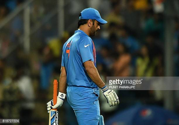 India's captain Mahendra Singh Dhoni walks back towards pavilion after his dismissal during the World T20 cricket tournament match between India and...