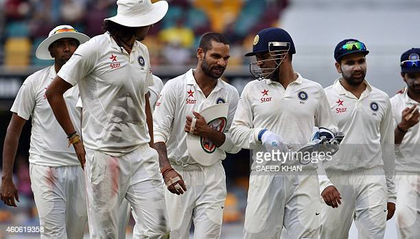 India's captain Mahendra Singh Dhoni walks off the ground with his players after bad light ended play during the second day of the 2nd cricket Test...