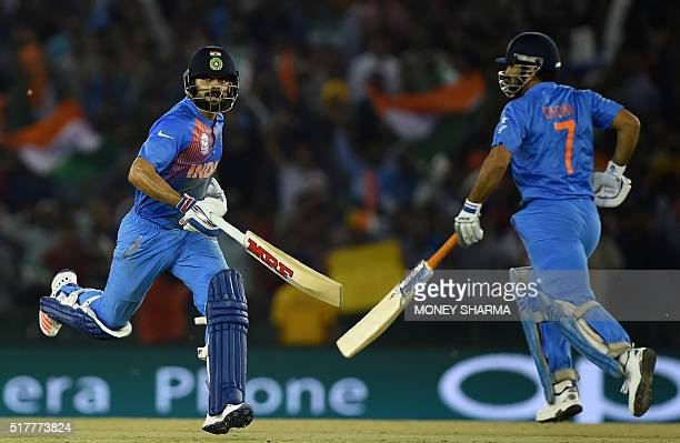India's captain Mahendra Singh Dhoniand teammate Virat Kohli run between the wickets during the World T20 cricket tournament match between India and...