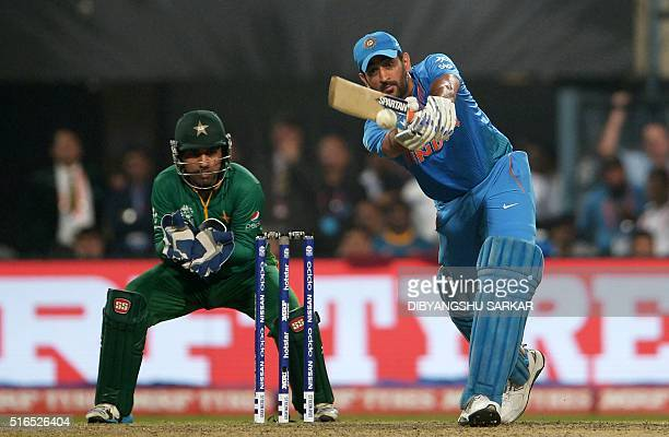 India's captain Mahendra Singh Dhoniis watched by Pakistan's wicketkeeper Sarfaraz Ahmed as he plays a shot during the World T20 cricket tournament...