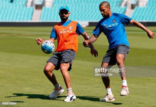 India's captain Virat Kohli and India's Shikhar Dhawan play football during a nets practice session at The Oval in London on June 17 on the eve of...