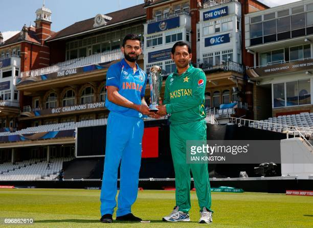 India's captain Virat Kohli and Pakistan's captain Sarfraz Ahmed hold the trophy as they pose for a photgraph at The Oval in London on June 17 on the...