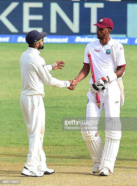 India's captain Virat Kohli and Roston Chase of the West Indies congratulate one another at the end of their match on day five of their Second Test...