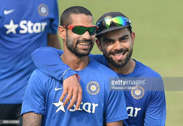 India's captain Virat Kohli and teammate Shikhar Dhawan interact after the warm up football game during a training session on the eve of the first...