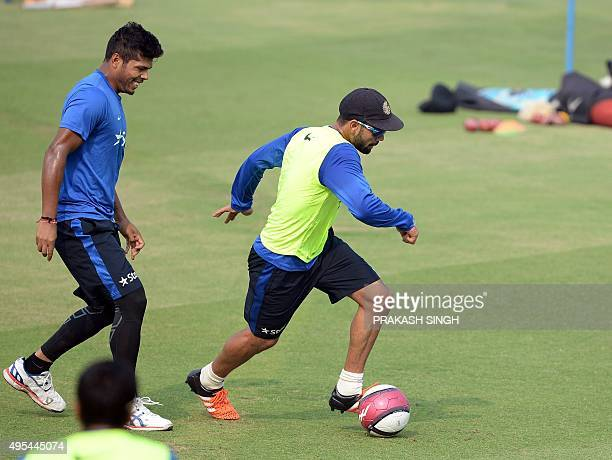 India's captain Virat Kohli and teammate Umesh Yadav play a warm up football match during a training session on the eve of the first Test match...