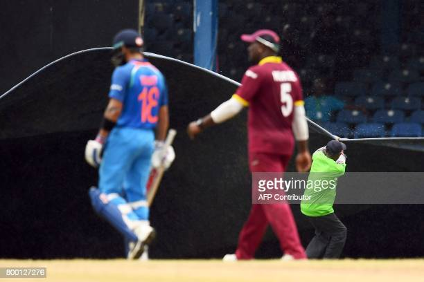 India's captain Virat Kohli and West Indies' Ashley Nurse leave the field as a groundsman pull a plastic sheet to cover the pitch during the first...
