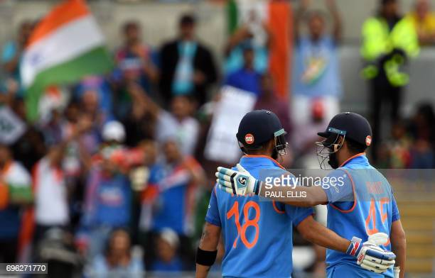 India's captain Virat Kohli celebrates with India's Rohit Sharma after reaching his 50 during the ICC Champions Trophy semifinal cricket match...