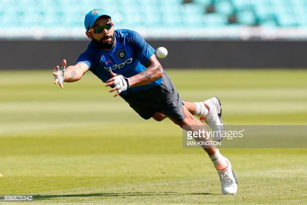 India's captain Virat Kohli dives to make a catch as he attends a nets practice session at The Oval in London on June 17 on the eve of the ICC...