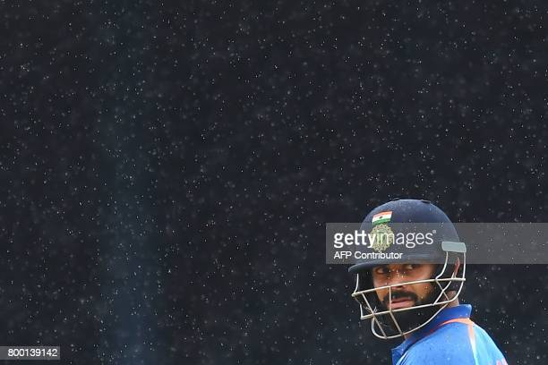 India's captain Virat Kohli leaves the field as rain interrupt the first One Day International match between West Indies and India at the Queen's...