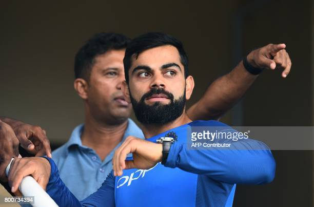 India's captain Virat Kohli looks at the wet ground as rain pours at the Queen's Park Oval in Port of Spain Trinidad on June 25 2017 Rain delayed the...