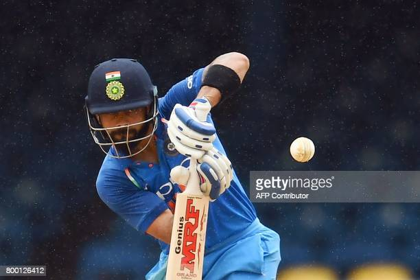 India's captain Virat Kohli plays a shot as it rain during the first One Day International match between West Indies and India at the Queen's Park...