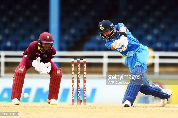 India's captain Virat Kohli plays a shot as West Indies' wicketkeeper Shai Hope looks on during the first One Day International match between West...