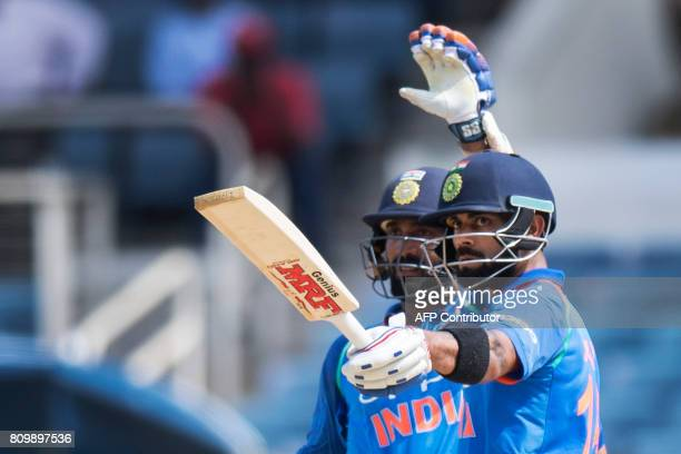 India's Captain Virat Kohli points his bat to the fans as he celebrates his 50 runs with teammate Dinesh Karthik during the fifth One Day...