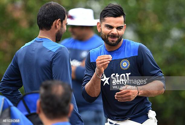 India's captain Virat Kohli shares a light moment with teammate Mohammed Shami during cricket training at the Sydney Cricket Ground on January 5 2015...