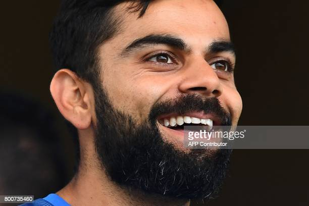India's captain Virat Kohli smiles as he talks with teammates before the start of the second One Day International match between West Indies and...