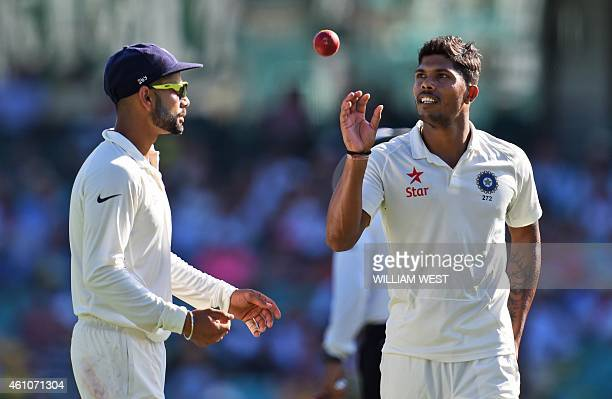 India's captain Virat Kohli tosses the ball to bowler Umesh Yadav on the first day of the fourth cricket Test against Australia at the Sydney Cricket...