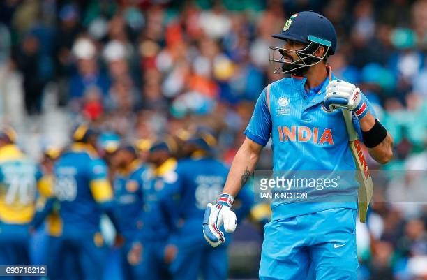 India's captain Virat Kohli walks back to the pavilion after losing his wicket for 0 runs to a catch by Sri Lanka's Niroshan Dickwella during the ICC...