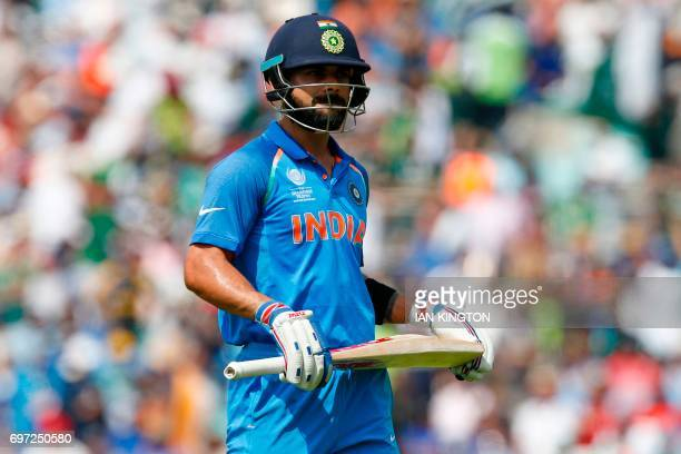 India's captain Virat Kohli walks back to the pavilion after losing his wicket during the ICC Champions Trophy final cricket match between India and...