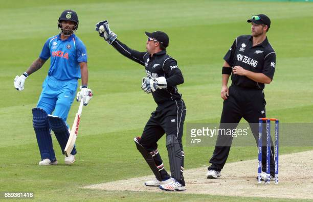 India's captain Virat Kohli watches as New Zealand's wicketkeeper Luke Ronchi takes a catch as New Zealand's Colin de Grandhomme looks on during the...