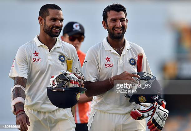 India's Cheteshwar Pujara and Shikhar Dhawan smile as they walk back to the pavilion at the end of play on the third day of the 2nd cricket Test...