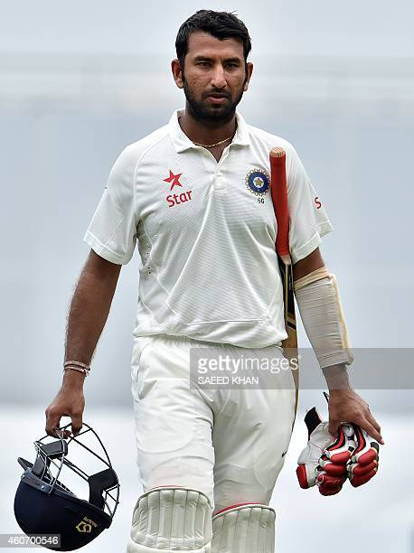 India's Cheteshwar Pujara walks off the field following his dismissal of Australia paceman Josh Hazlewood on the fourth day of the 2nd cricket Test...