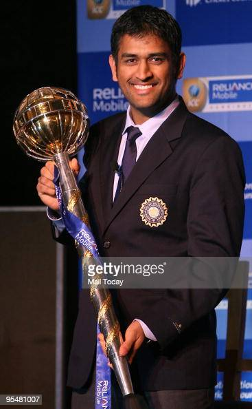 India's cricket captain Mahendra Singh Dhoni poses with International Cricket Council's test championship mace at a felicitation function in New...