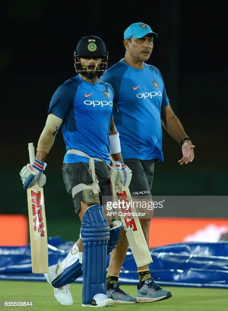 India's cricket captain Virat Kohli and coach Ravi Shastri walks during a practice session at the Rangiri Dambulla International Cricket Stadium in...