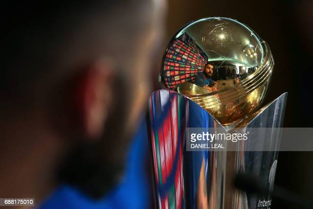 India's cricket captain Virat Kohli is reflected in the trophy as he addresses a press conference in The Grange in London on May 25 ahead of the ICC...