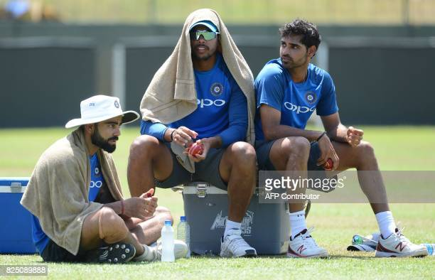 India's cricket captain Virat Kohli with teammate Umesh Yadav and Bhuvneshwar Kumar rest during a practice session at the Sinhalease Sports Club...