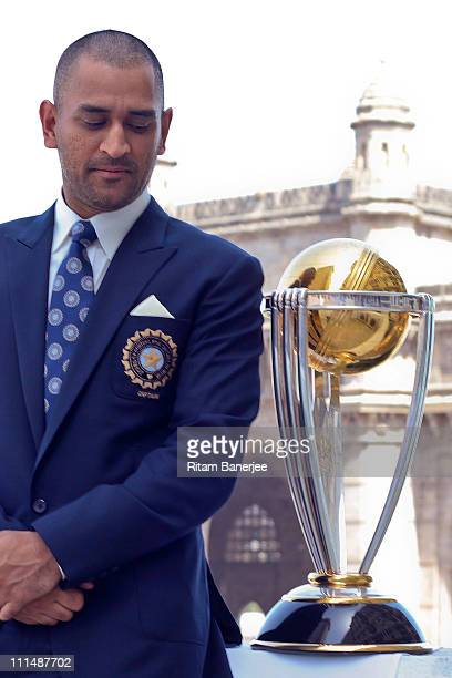 India's cricket team captain Mahendra Singh Dhoni poses with the ICC Cricket World Cup Trophy with the Gateway of India in the backdrop during a...