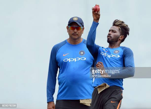 India's cricketer Hardik Pandya delivers a ball as coach Ravi Shastri look on during a practice session at the Sinhalease Sports Club Ground in...