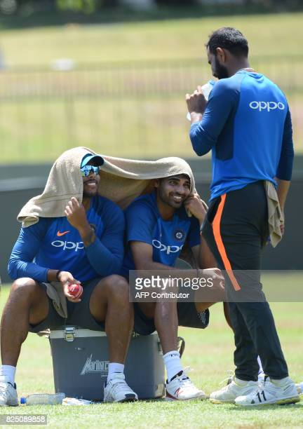 India's cricketer Mohammed Shami speaks with teammates Umesh Yadav and Bhuvneshwar Kumar at a practice session at the Sinhalease Sports Club Ground...