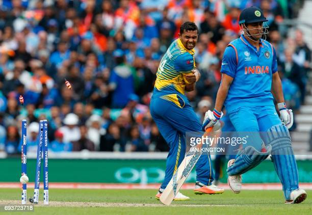 India's MS Dhoni barges past Sri Lanka's Asela Gunaratne to reach his crease and avoid losing his wicket during the ICC Champions Trophy match...